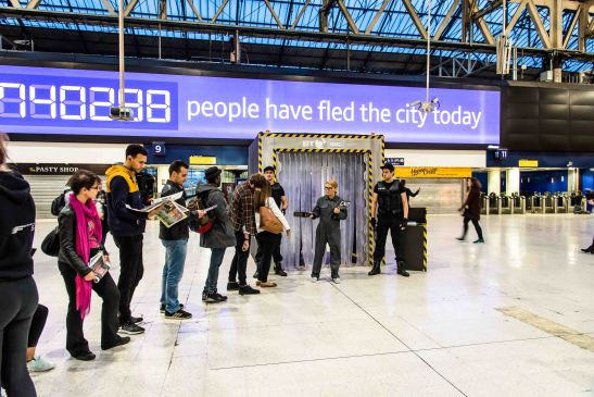 """Commuters ready to leave London queue at Waterloo station to be scanned for infection to mark the launch of """"Fear the Walking Dead"""" exclusively on AMC from BT"""